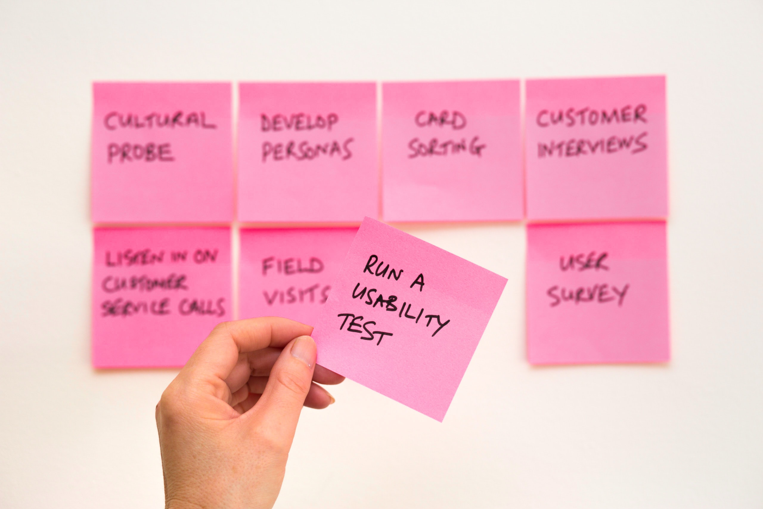 Post-it notes list actions to include as a UX writer developing a content strategy: cultural probe, develop personas, card sorting, customer interviews, listen in o customer service calls, field visits, run a usability test, and user survey